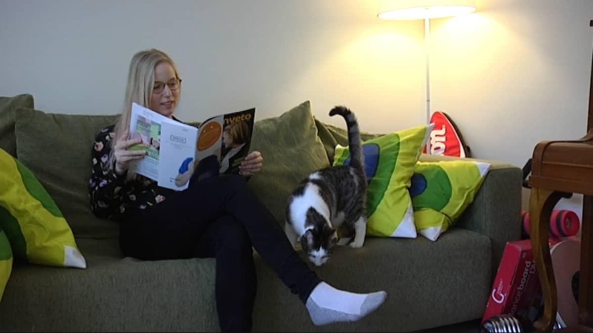 Opiskelija lukee lehteä sohvalla.