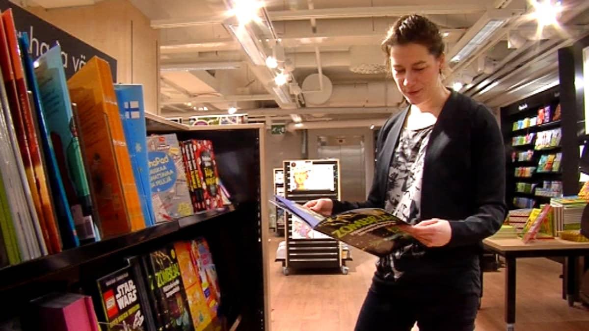 Susanne Ylönen selailee zombi-kirjaa kirjakaupassa.