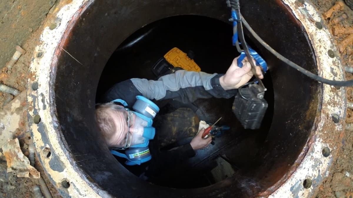 Työmies tarkastaa pientalon öljysäiliötä.
