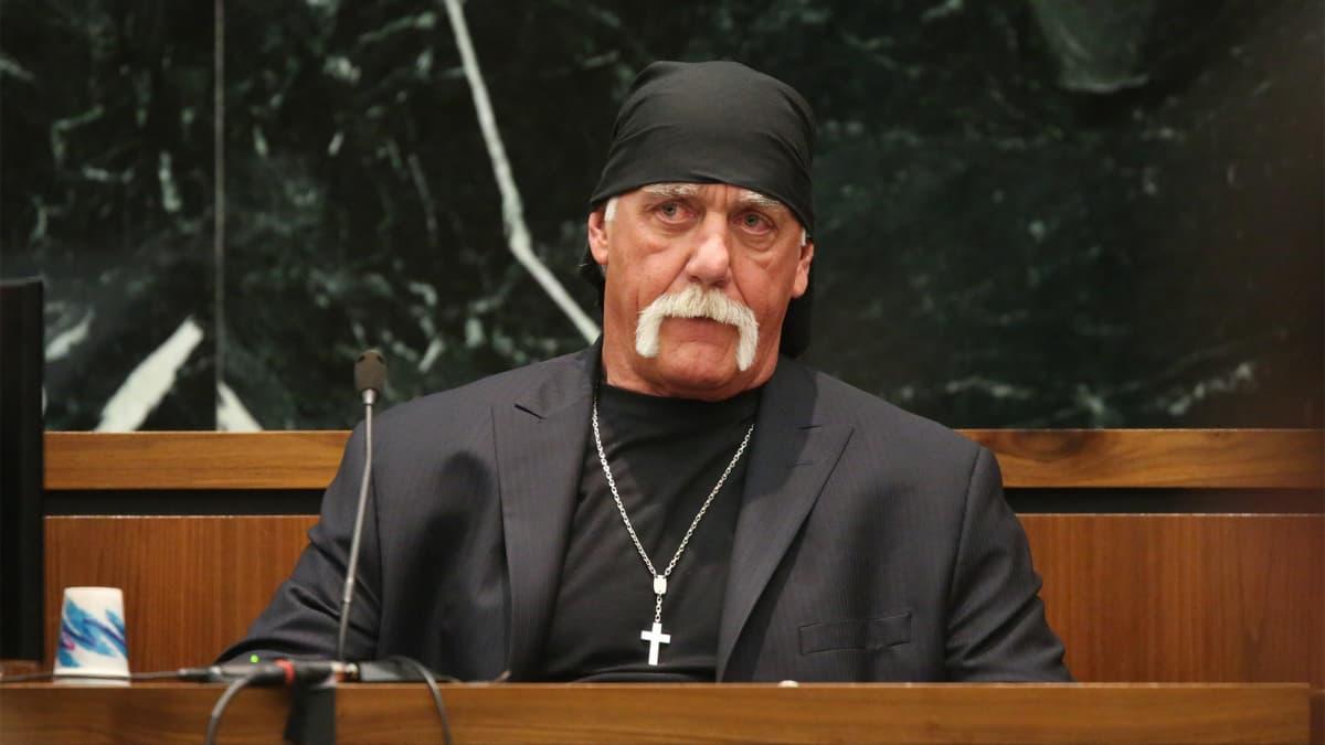 Mies mustassa puvussa ja mustassa päähineessä.