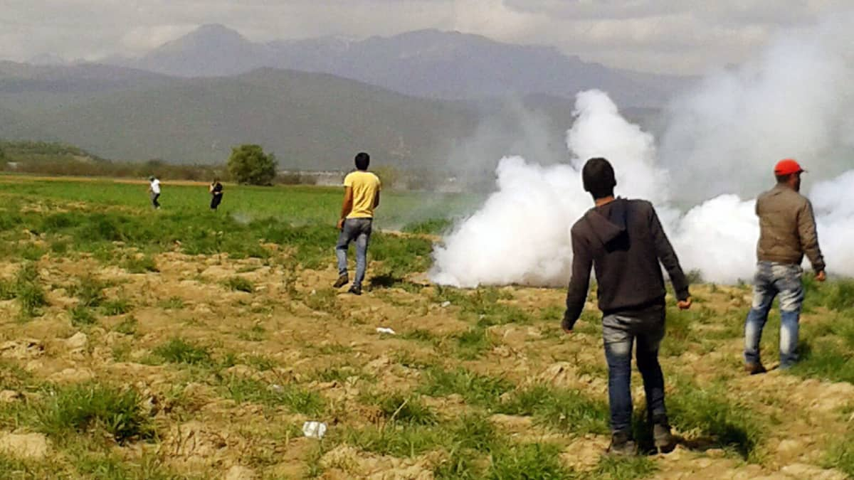 Turvapaikanhakijat väistelevät kyynelkaasua lähellä Makedonian rajaa Kreikan Idomenissa.