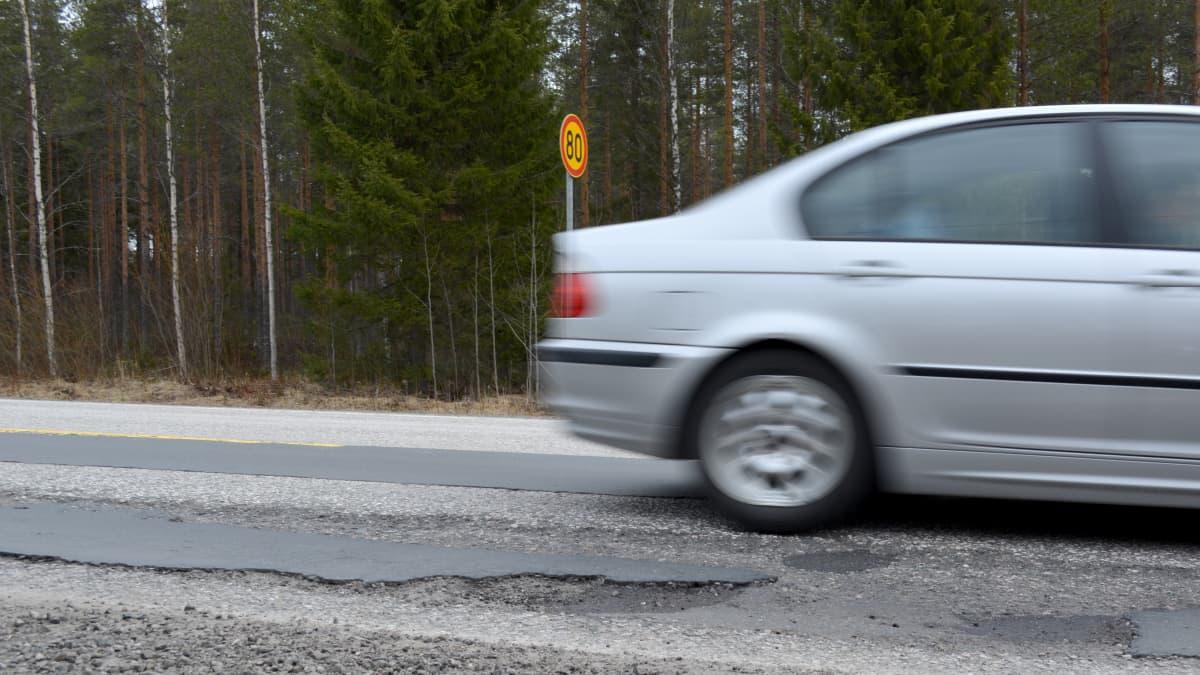 Auto ajaa huonokuntoista tietä.