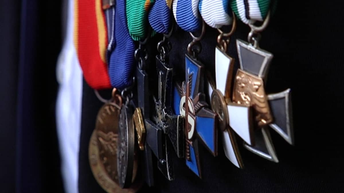 Rivi ansiomitaleja sotaveteraanin puvun rintamuksessa.