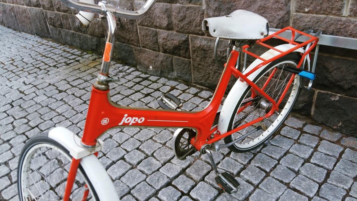 Jopo-pyörä lukittuna takarenkaasta telineeseen.