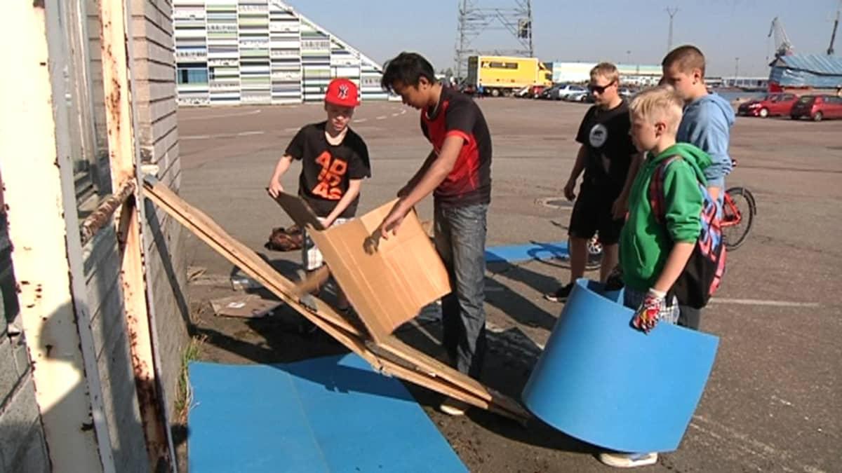 Kotkan Helilän koulun nuoret tehtävärastilla rakentamassa pikamajaa annetuista aineista.