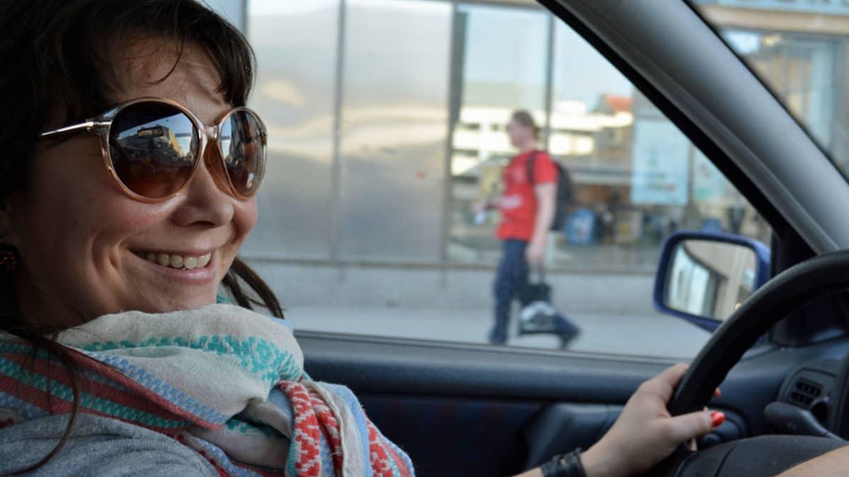 Nainen ajaa autoa.
