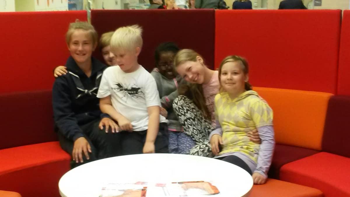 Kuusi lasta istuu sohvalla iloisin ilmein.