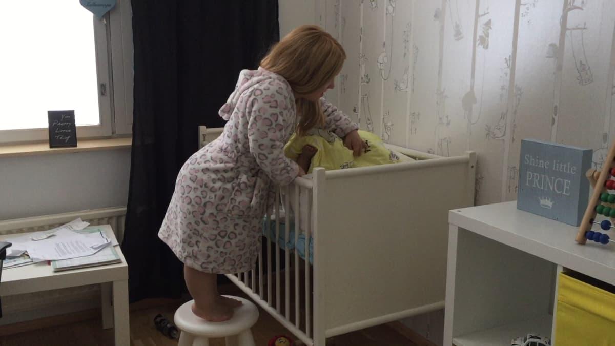Milla Maria Lassila peittelee lasteen pinnasänkyyn.