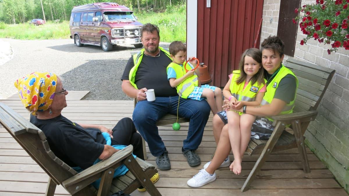 Mies ja kaksi naista istuu kahvilla terassilla. Sylissä on kaksi lasta.