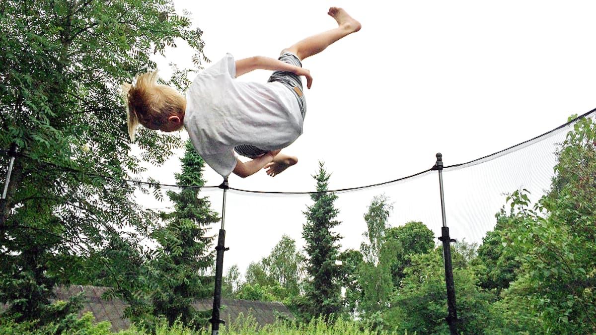 Lapsi hyppää trampoliinissa