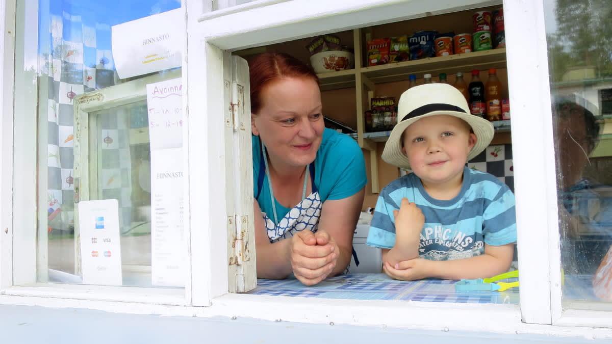 Lippalakkipäinen pikkupoikaja naismyyjä kioskin luukulla
