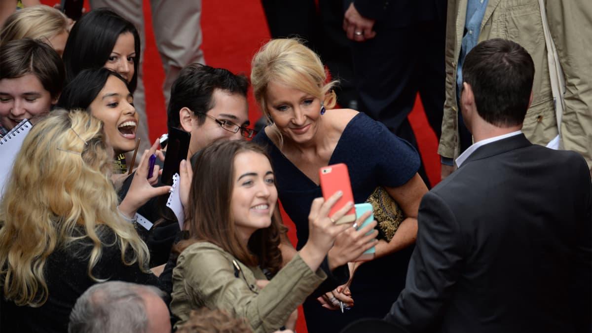J.K. Rowling poseeraa fanien kanssa selfieen.