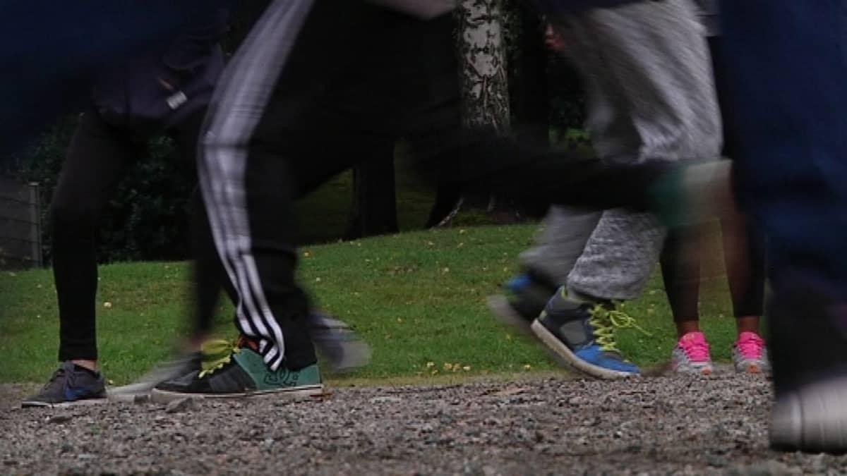 Yläkoululaiset juoksevat hiekkakentällä.