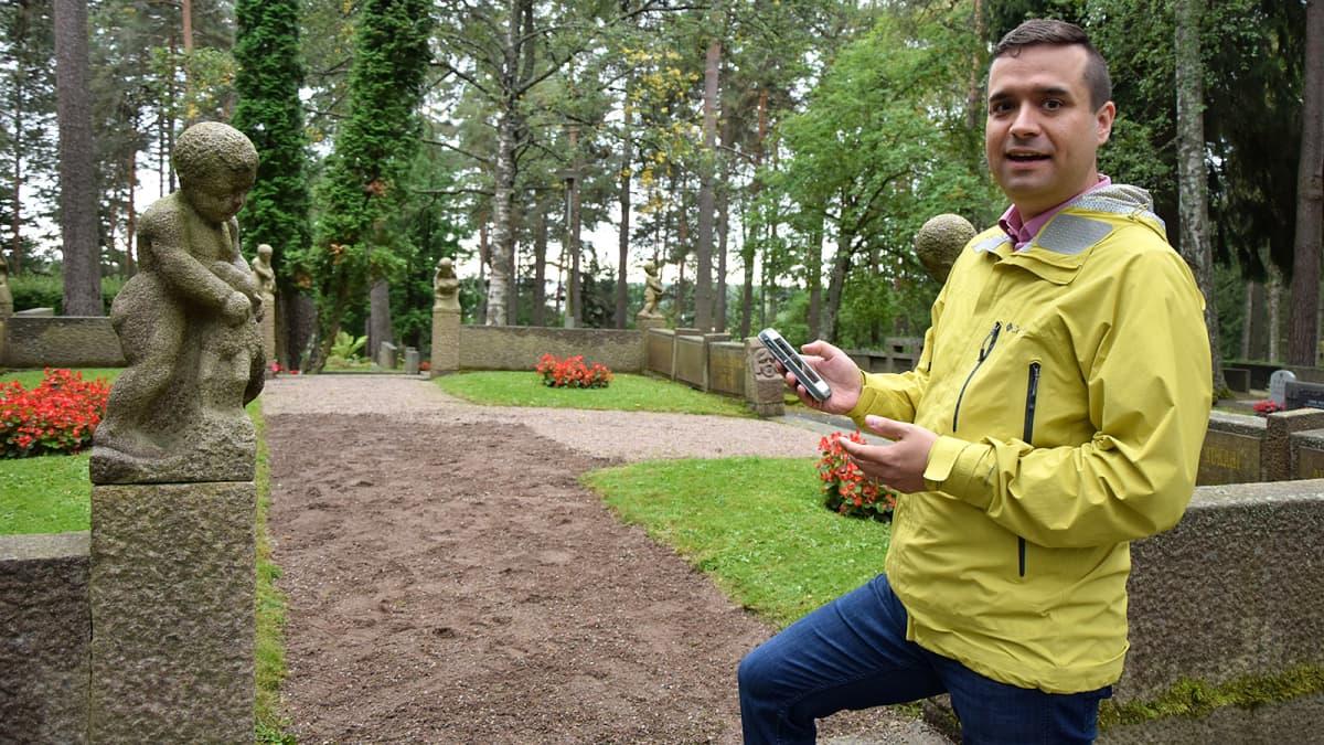 Mies selaa virtuaaliopasta kännykästään hautausmaalla