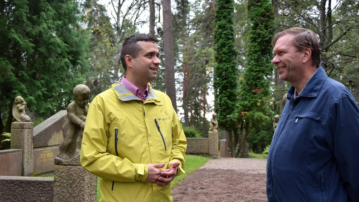 Kaksi miestä juttelee hautausmaalla