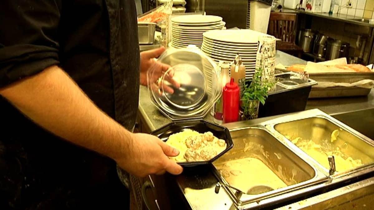 Ravintolan keittiössä pakataan lounasruokaa noutoannoksiin.