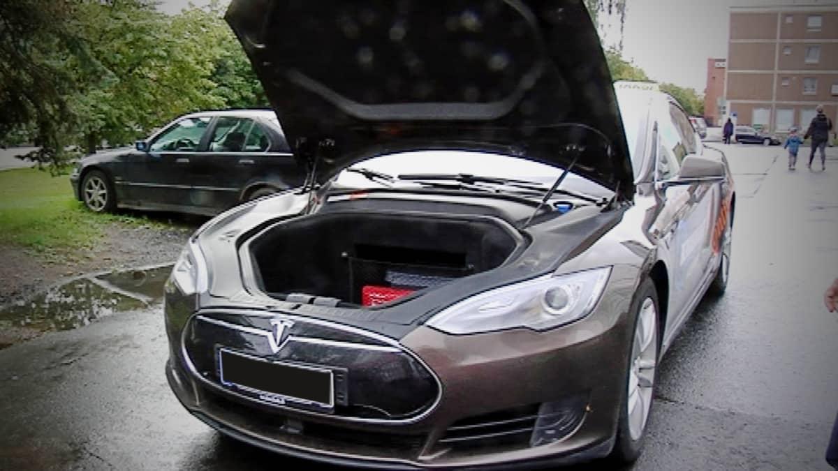 Harmaa sähköautoa Tesla konepelti auki parkkeerattuna kadulle.