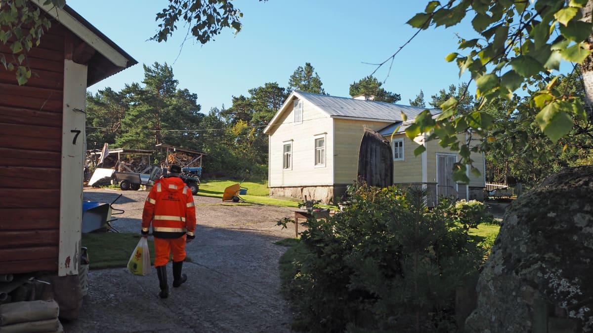 Mies kävelemässä kotitaloonsa