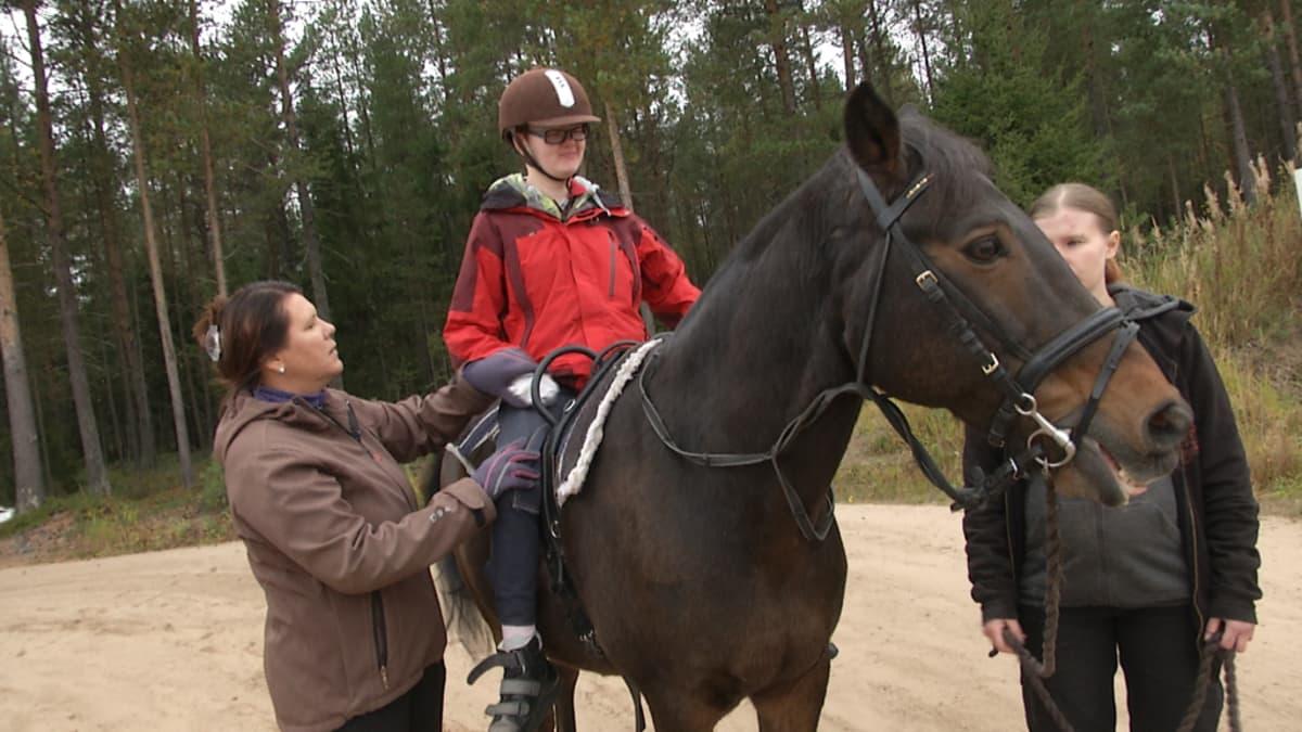 Ratsastusterapeutti auttaa hevosen selässä olevaa kuntoutettavaa