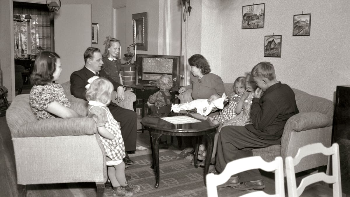 Perhe on kokoontunut kuuntelemaan radiota.