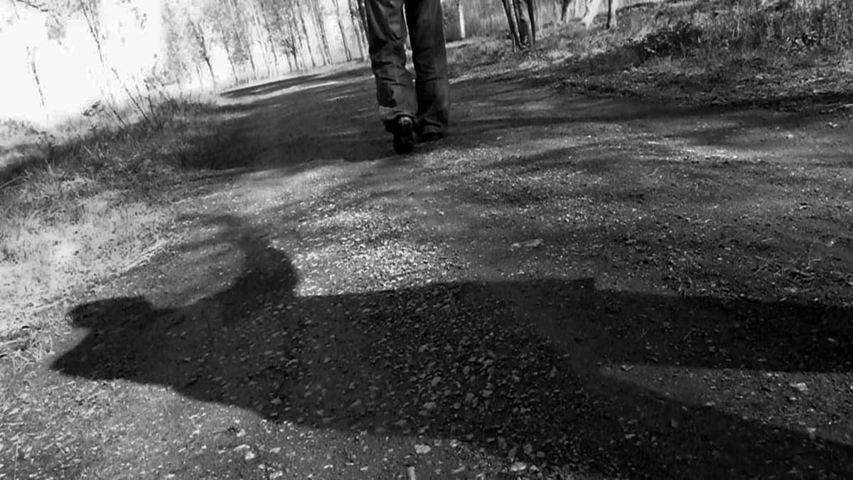 Henkilö kulkee polulla, takana uhkaava varjo