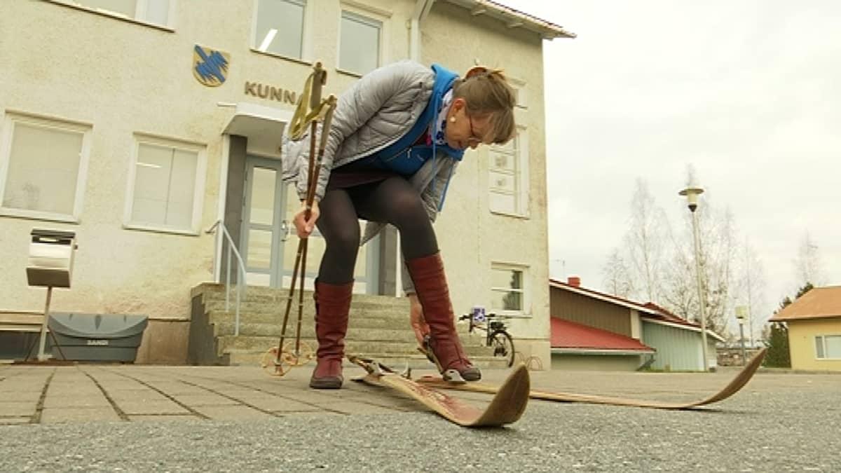 Kunnanjohtaja Kirsi Virtanen laittaa suksia jalkaan Jämijärven kunnnatalon edustalla.