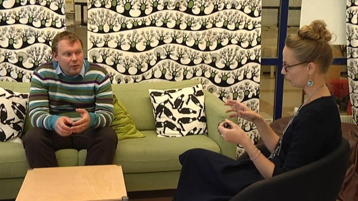 Sohvalla istuva mies keskustelee tuolilla istuvan naisen kanssa.