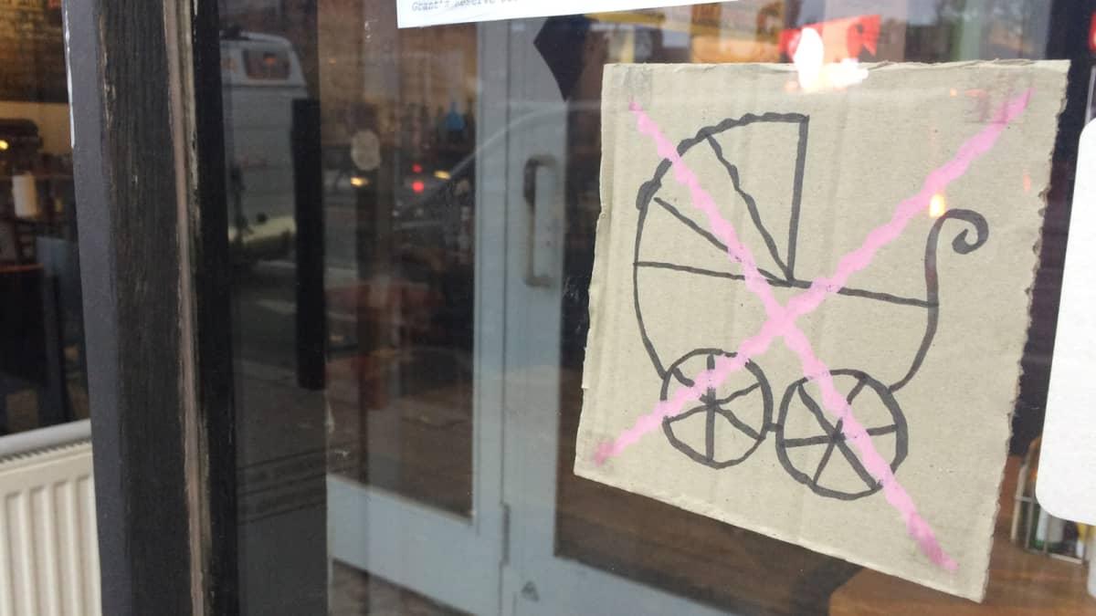 Vaunut kieltävä kyltti ravintolan ovessa