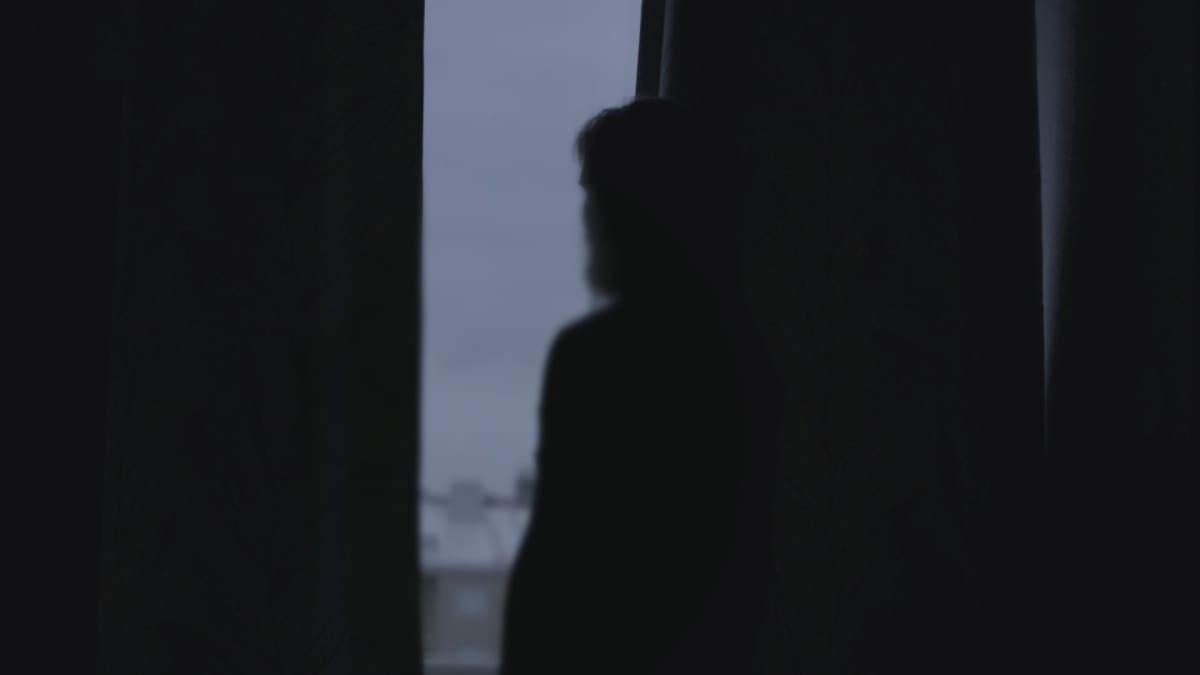Mies ikkunan edessä.
