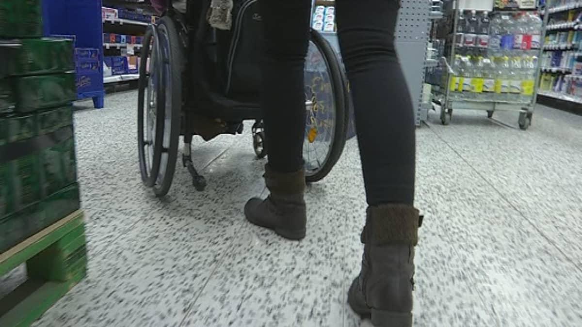 Henkilöhtainen avustaja työntää avustettavan pyörätuolia kaupassa.