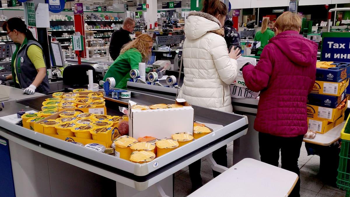 Venäläisiä ostamassa juustoa kaupan kassalla.
