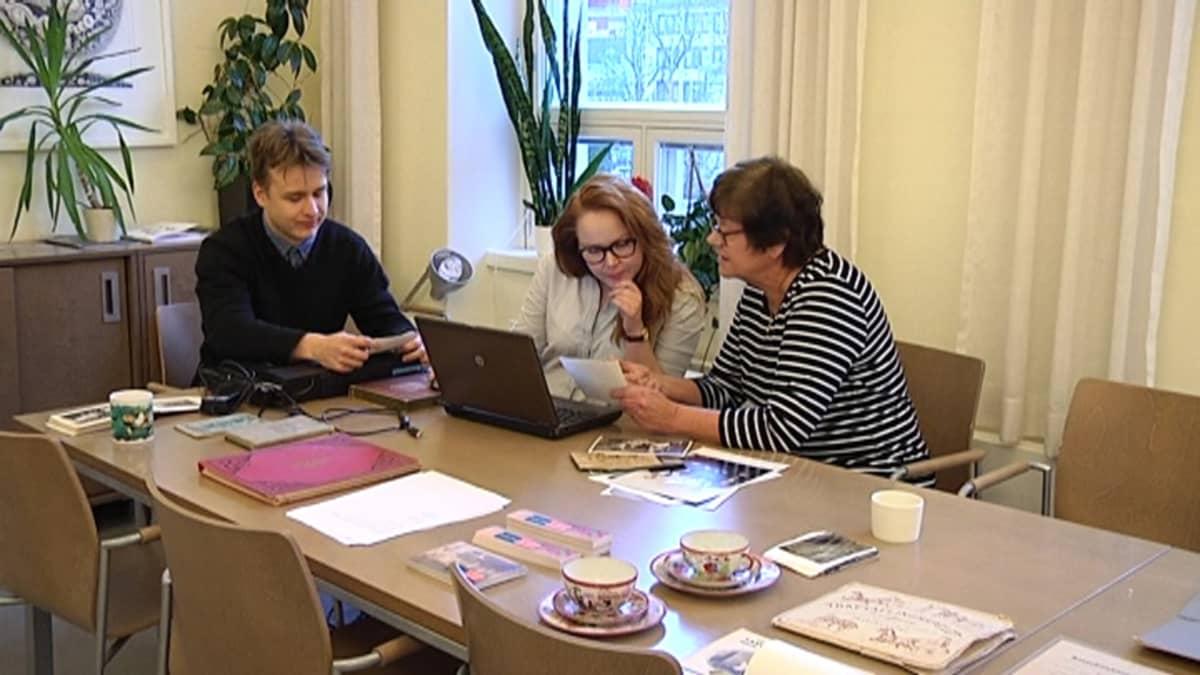 Tutkijat katsovat valokuvia pöydän ääressä  yhdessä turkulaisen naisen kanssa