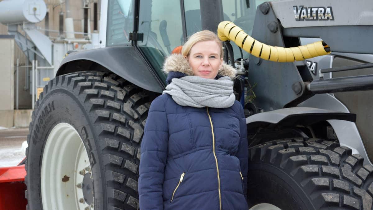 Nainen seisoo teollisuusalueella traktorin edessä.