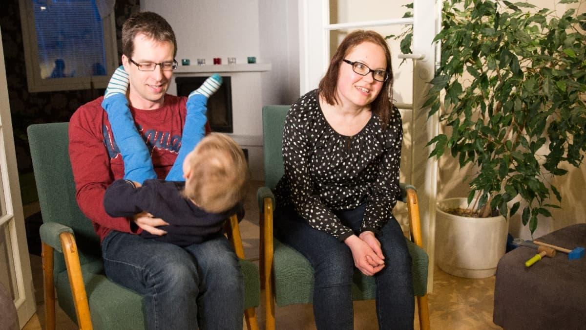 Pikkupoika keikkuu isän sylissä, äiti istuu vieressä.