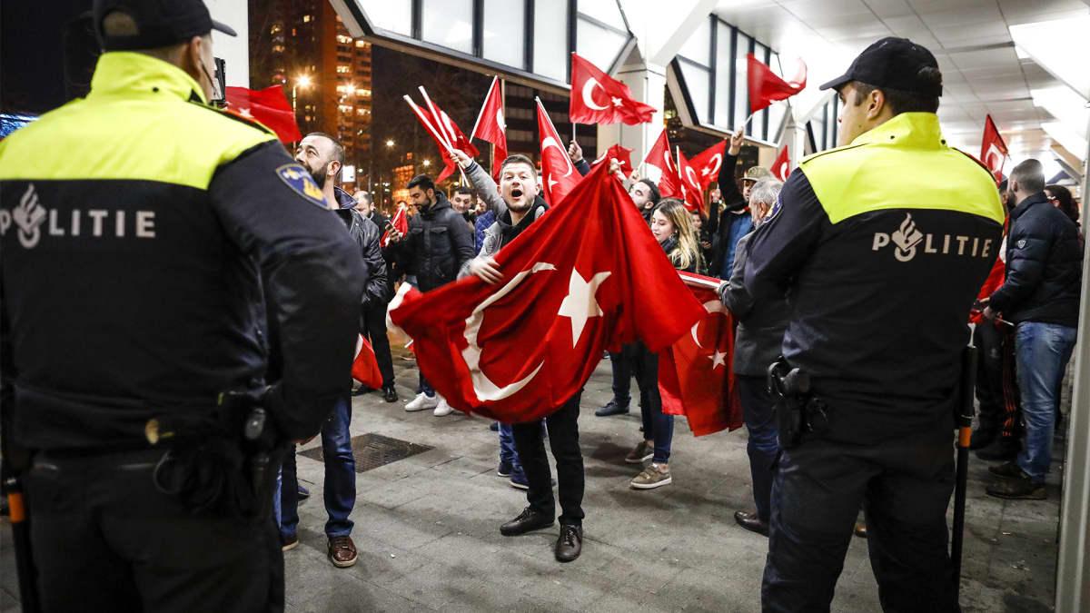 Kaksi poliisia ja lukuisia turkin lippua heiluttavia mielenosoittajia.