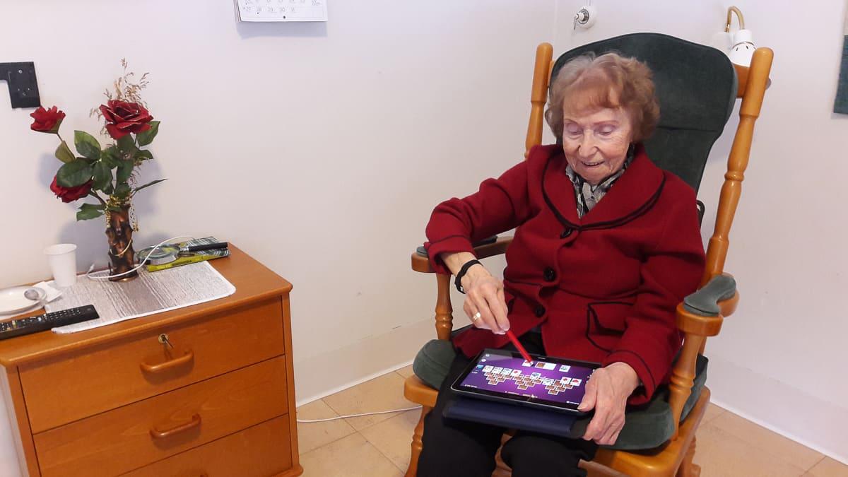 Irma Karppi pelaa pasianssia tablettitietokoneella.