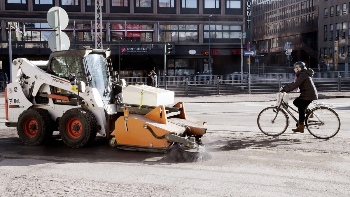 Lakaisukone puhdistaa jalkakäytävää hiekoitushiekasta ja katupölystä Arkadiankadulla Helsingissä.