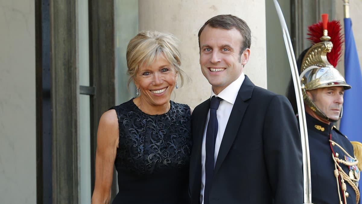 Brigitte Trogneux ja Emmanuel Macron vierekkäin palatsin ovella. Taustalla näkyy perinteisessä paraatiunivormussa oleva sotilas, joka pitää miekkaansa paljastettuna.