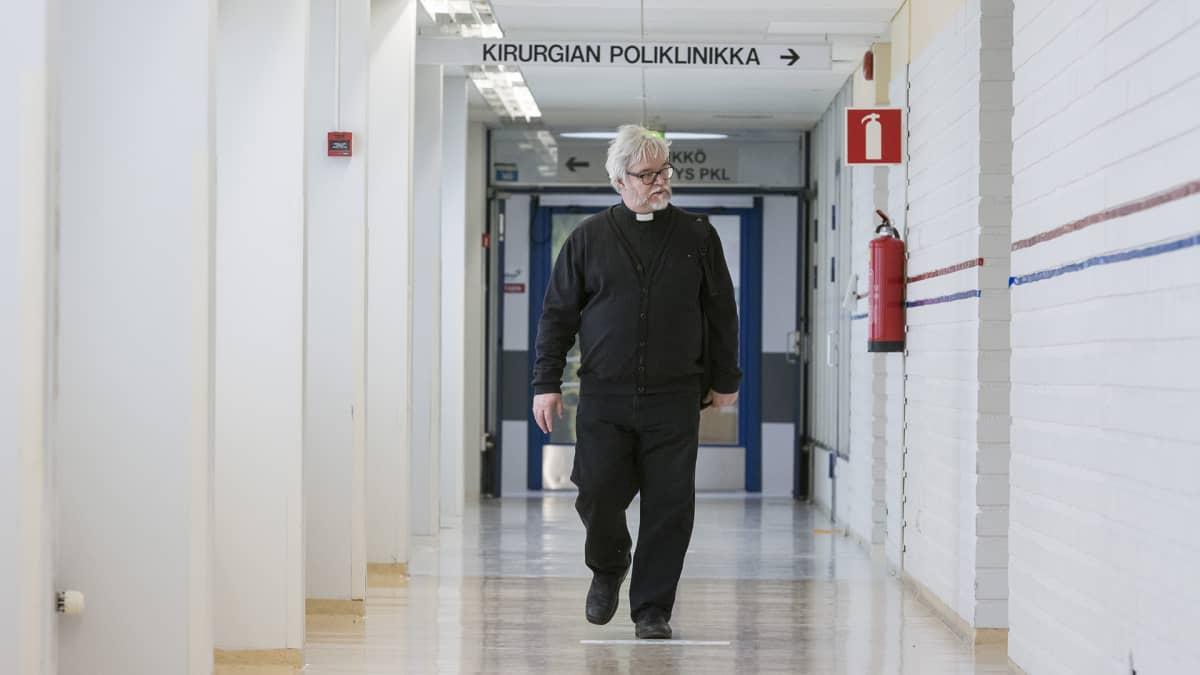 Pappi kävelee sairaalan käytävällä