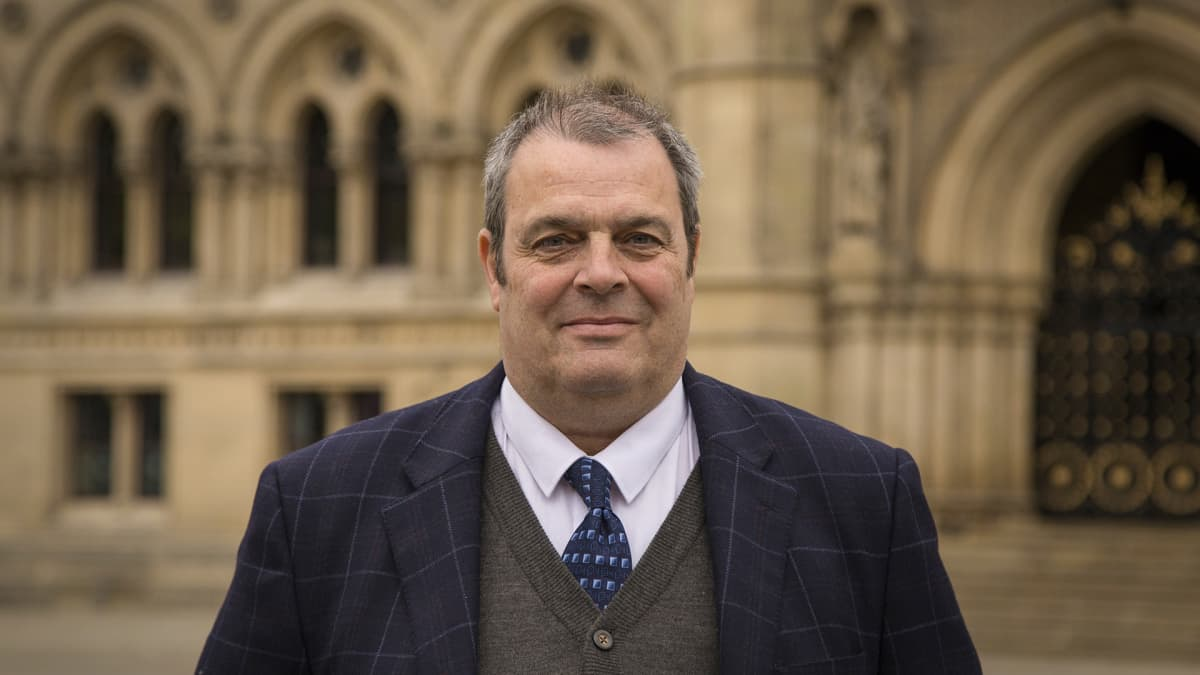 Siniseen ruudulliseen puhuun pukeutunut, hieman harmaantunut, keski-ikäinen mies Bradfordin kaupungintalon edustalla.