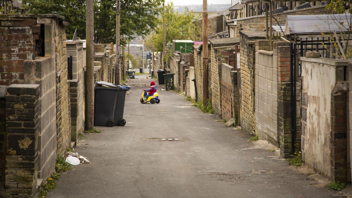 Pieni lapsi muovimopolla ajamassa talojen takana olevalla kävelykujalla, jossa on roskiksia ja roskaa kaduilla.