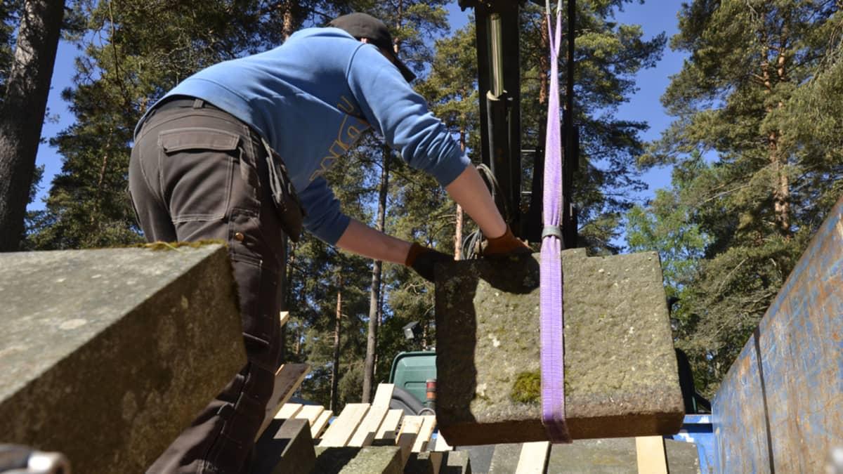 Vanhaa hautakiveä lastatataan kuorma-auton lavelle varastoon kuljetusta varten.
