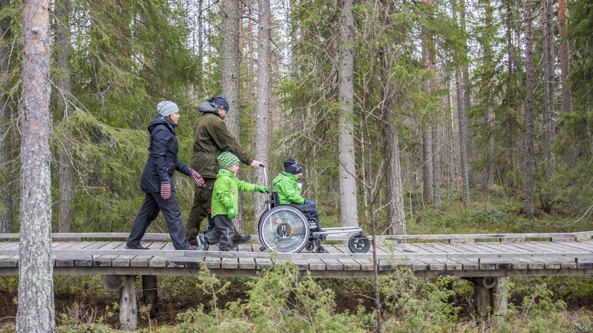 Kähköset kulkevat luonnossa pyörätuolin kanssa.