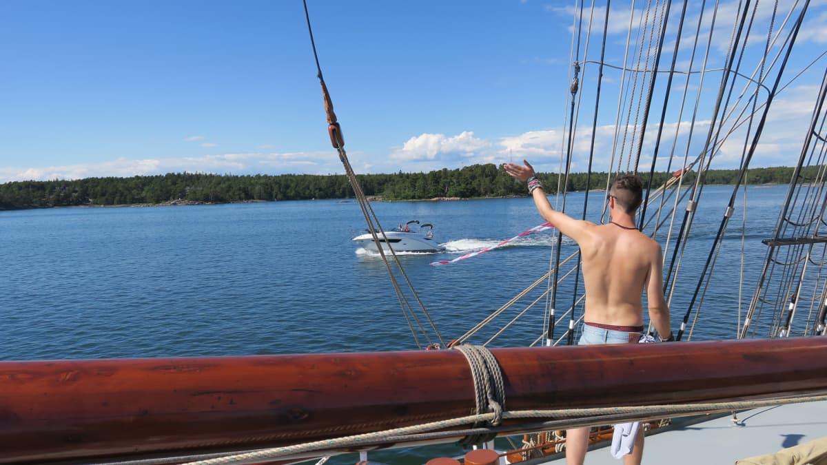 Korkeamastoinen Morgenster on upea ilmestys saariston asukkaille. Veneet kiertelevät purjealusta, ja ihmiset vilkuttavat niistä mennessään.