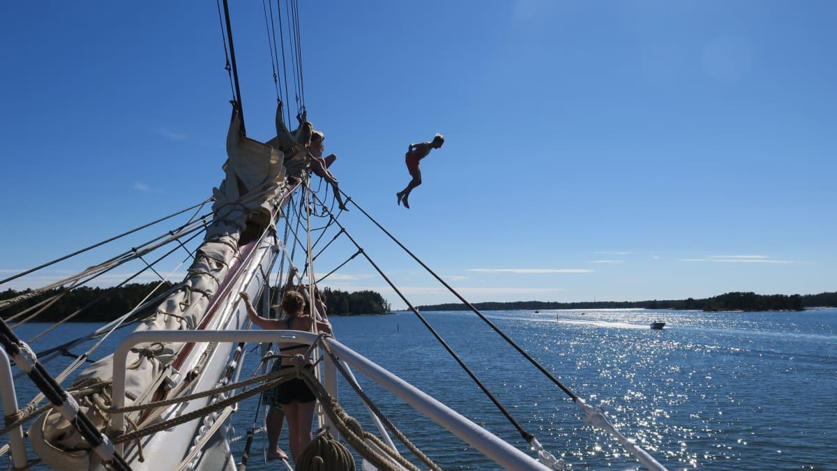 Nuoret kiipeävät keulapuomiin ja hyppäävät alas veteen, joka tuntuu viileältä.