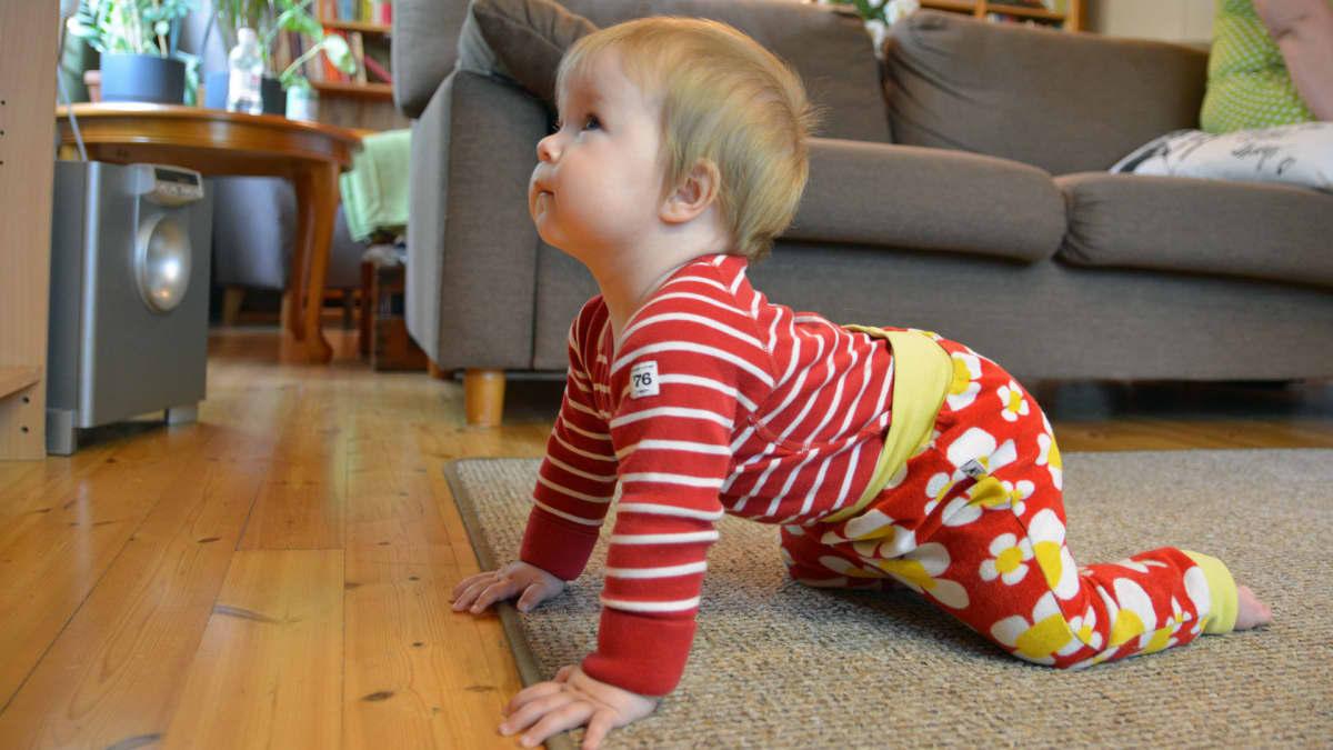 Pieni lapsi on television edessä lattialla.