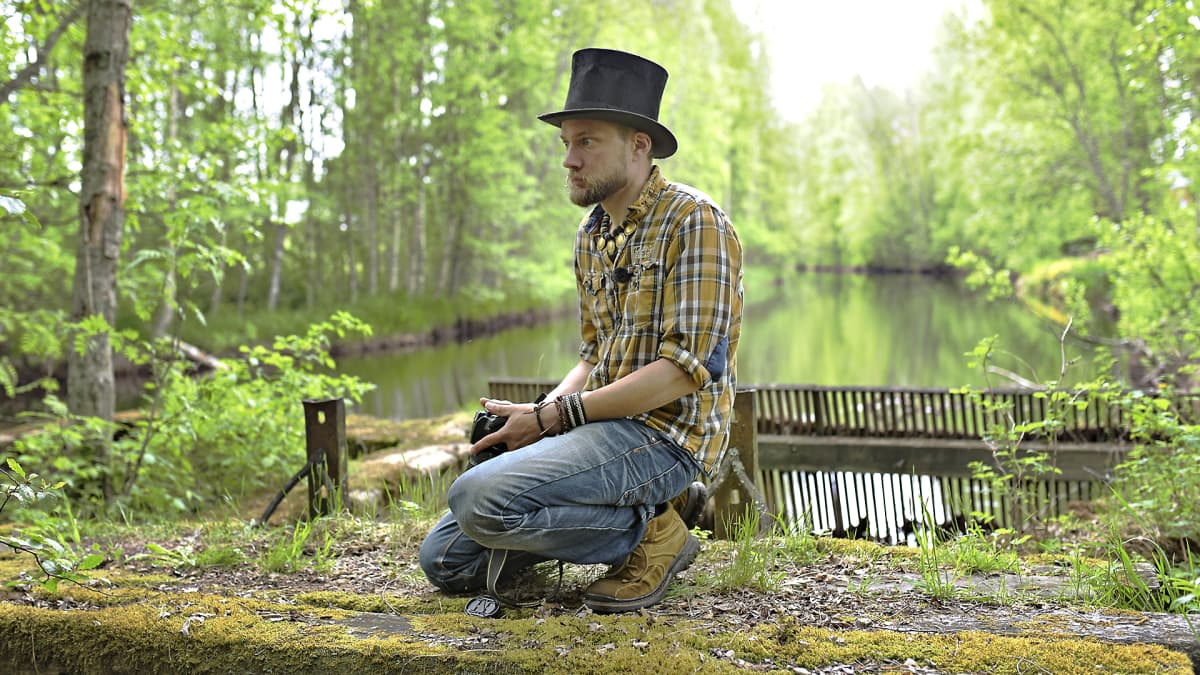 Juha Järvinen istuu sammaloituneella sillalla.
