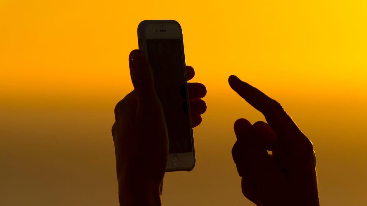 Käsi näppäilee kännykkää.