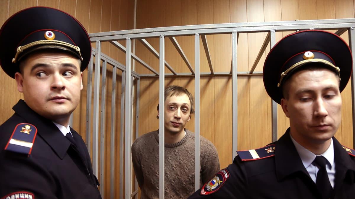 Pavel Dmitrichenko häkissä poliisien vartioimana.