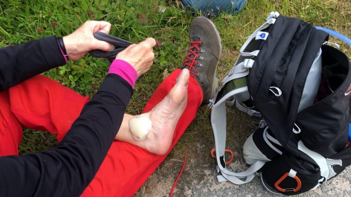 Nainen laittaa sukkaa jalkaansa.